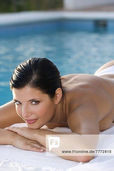 Junge Frau am Pool liegend
