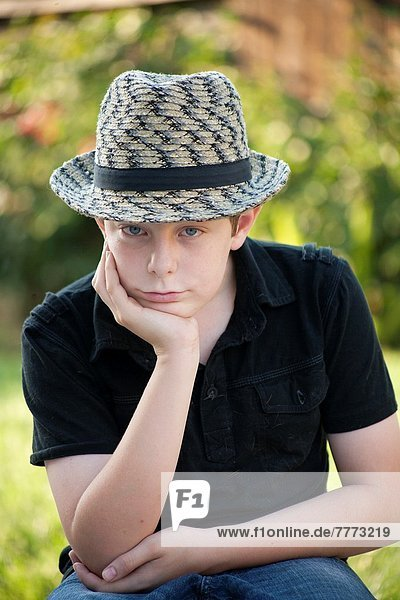 young boy sitting staring at camera with a grumpy face