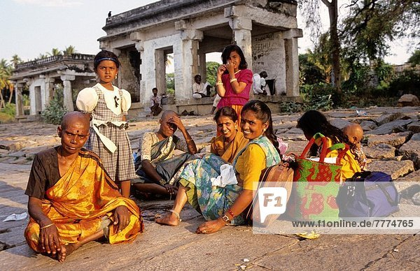 Indian women sitting in front of a temple