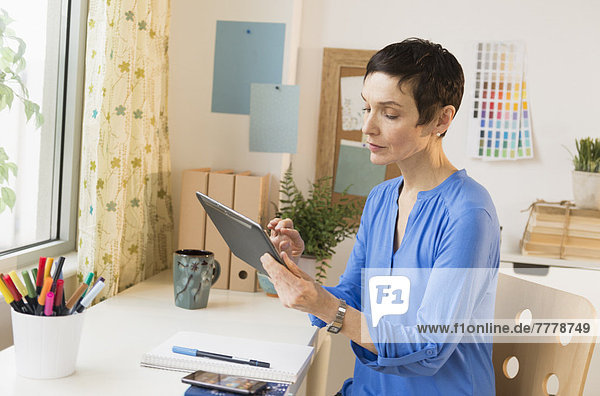 Woman using digital tablet in home office