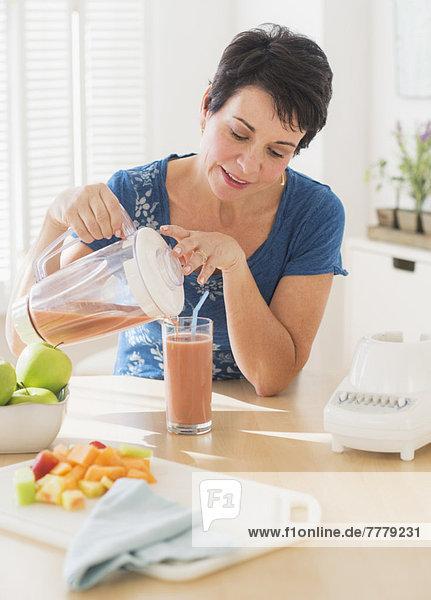 Portrait  Frau  Glas  eingießen  einschenken  reifer Erwachsene  reife Erwachsene  Mixer  smoothie