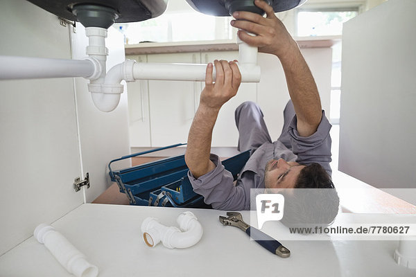 Plumber working on pipes under kitchen sink