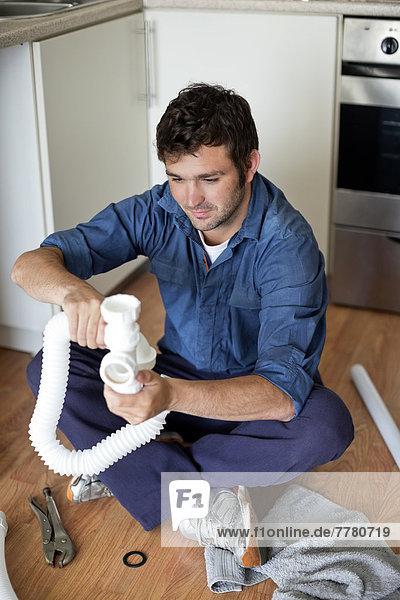 Klempnerarbeiten an Rohren unter der Küchenspüle