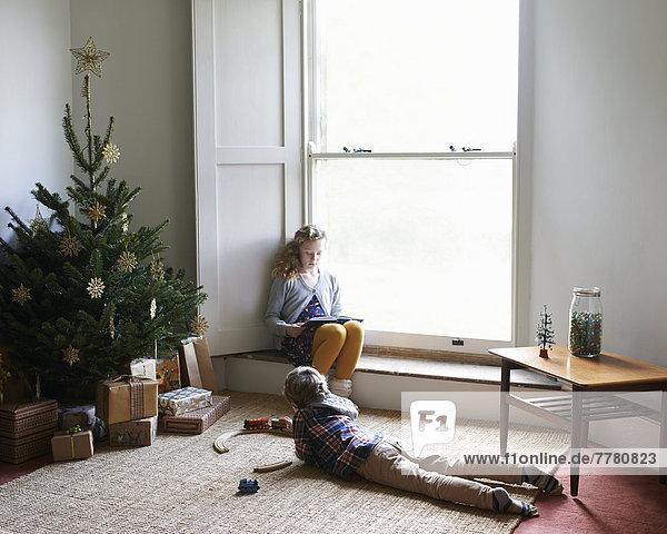 Kinder entspannen sich am Weihnachtsbaum