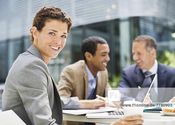 Geschäftsfrau lächelt in einer Besprechung im Freien
