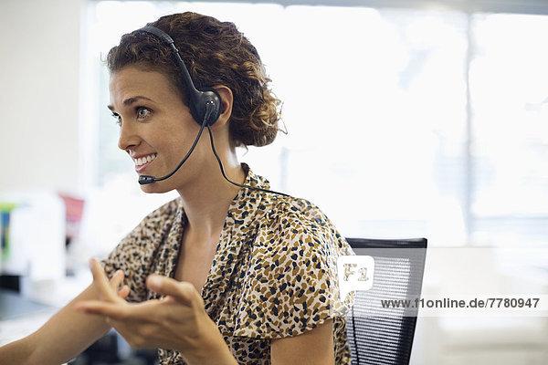 Geschäftsfrau spricht am Schreibtisch am Headset