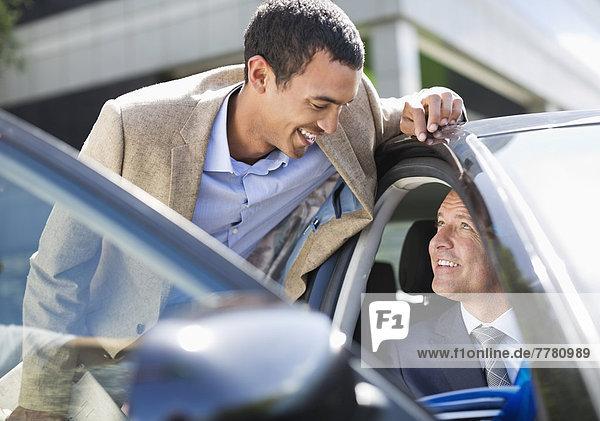 Businessmen talking in car