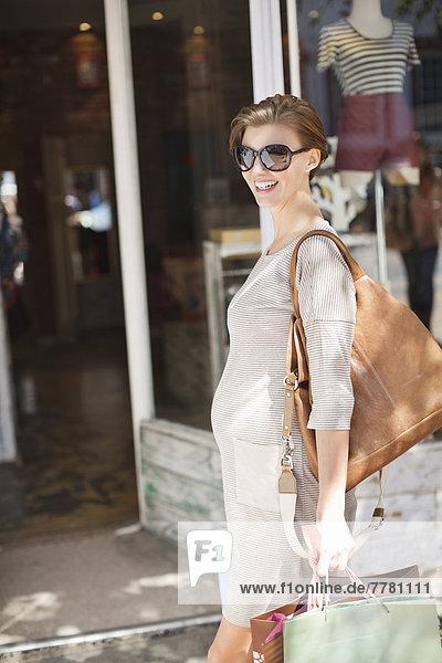 Schwangere Frau beim Einkaufen in der City Street