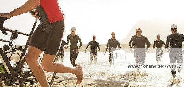 Triathleten  die aus dem Wasser auftauchen