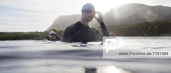 Triathleten in Trikots im Wasser stehend