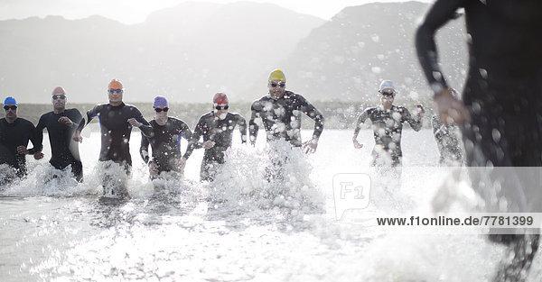 Triathleten in Trikots  die in Wellen laufen