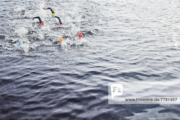 Triathleten spritzen im Wasser