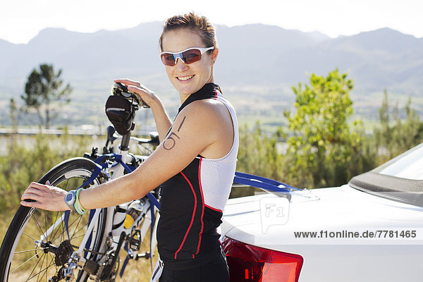 Woman attaching bicycle to car