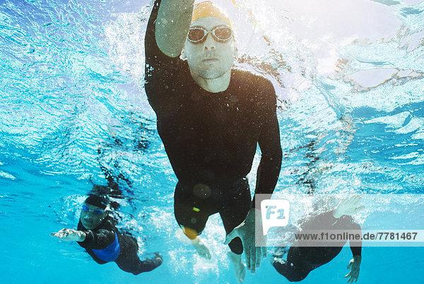 Triathleten in Trikots unter Wasser