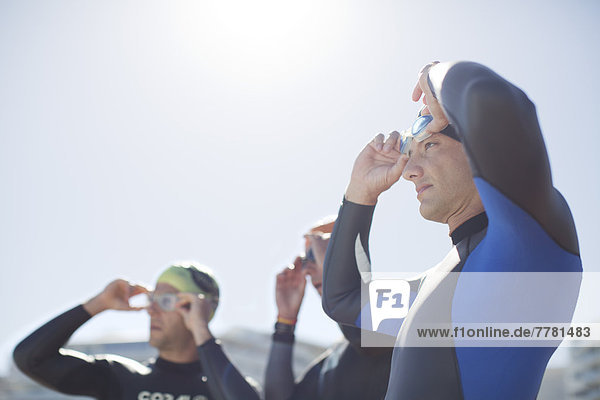 Triathletinnen und Triathleten  die ihre Brille im Freien anpassen