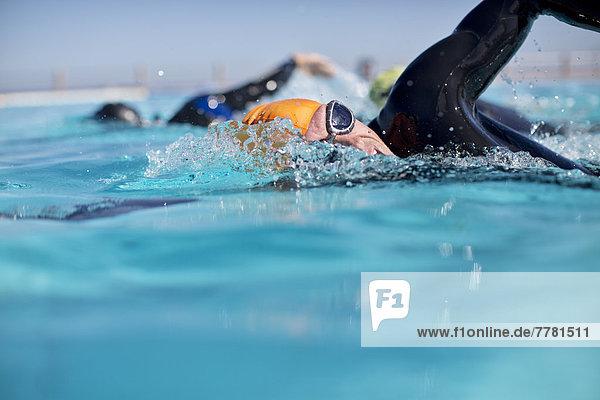 Triathleten im Trikostüm planschen im Pool