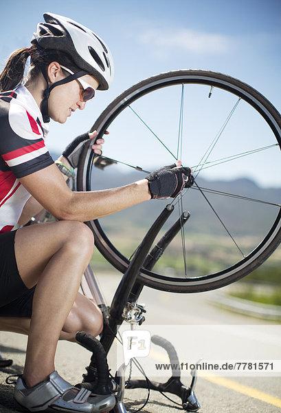 Radfahrer beim Einstellen von Reifen auf der Landstraße
