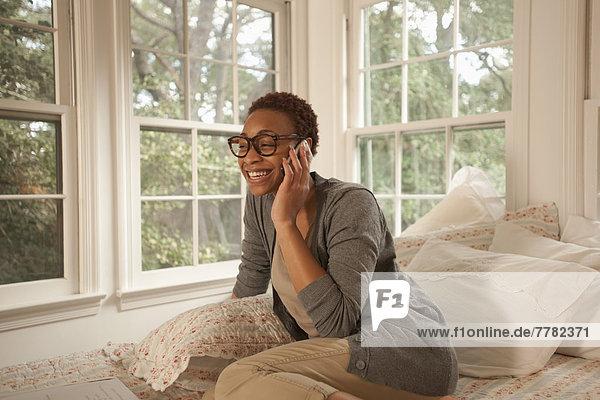 Handy  sitzend  Frau  sprechen  Bett  amerikanisch