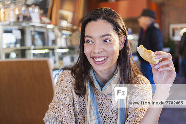 Mixed race woman eating in coffee shop