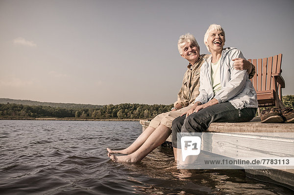 Older Caucasian couple sitting on wooden dock