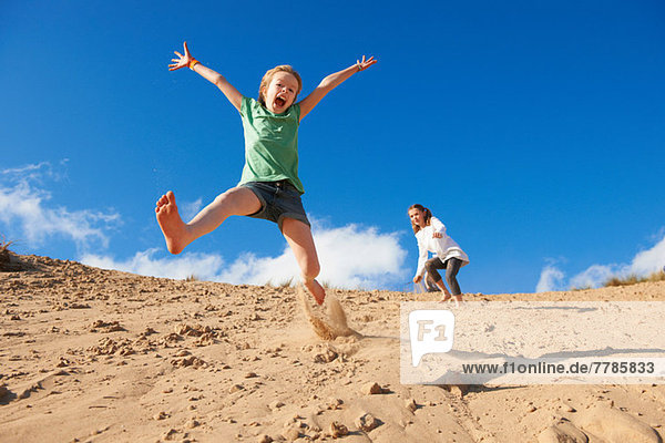 Zwei Mädchen beim Springen am Strand