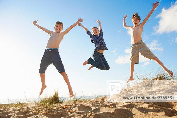 Jungen und Teenager-Mädchen springen am Strand