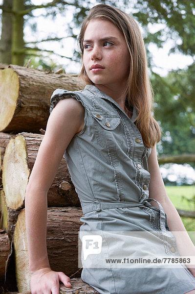 Teenager-Mädchen  das sich im Wald auf Baumstämme stützt.