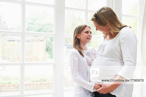 Schwangere Mutter mit jugendlicher Tochter am Fenster