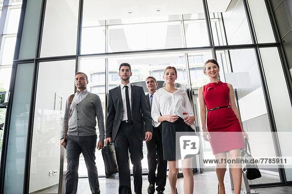 Gruppe von Geschäftsleuten betritt Bürogebäude aus Glas
