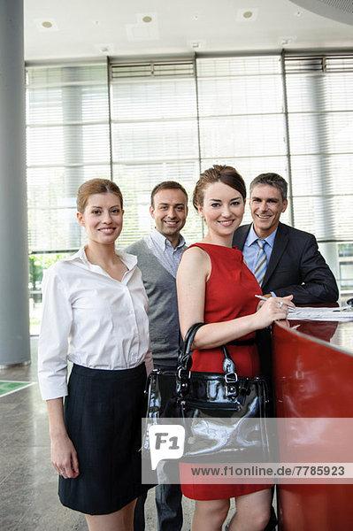 Gruppe von Geschäftsleuten mit Dokumenten an der Rezeption