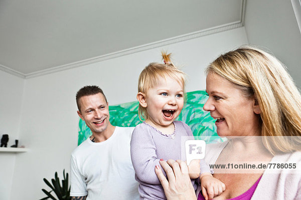 Mother and father with toddler daughter  smiling