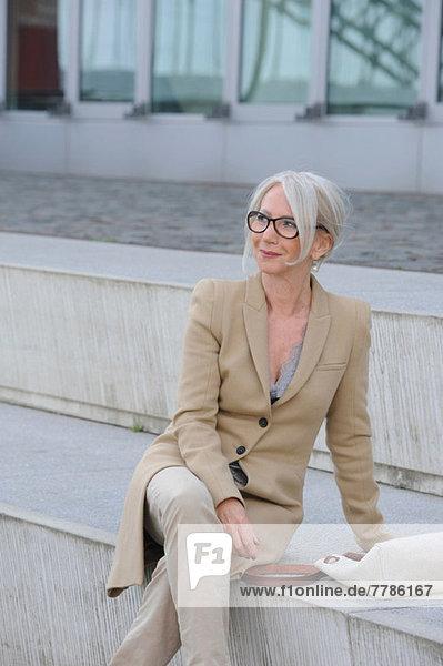 Seniorin sitzend auf einer Treppe in der Stadt