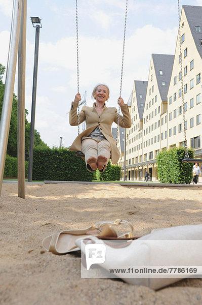 Seniorin auf Spielplatzschaukel