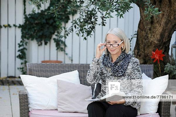 Porträt einer älteren Frau mit Buch im Garten