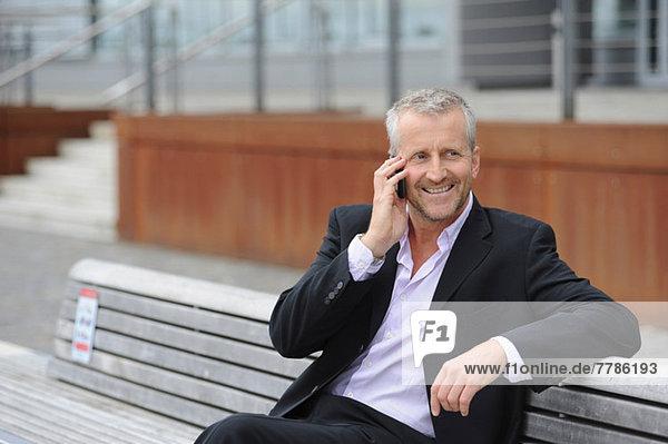 Reifer Mann beim Telefonieren auf der Bank