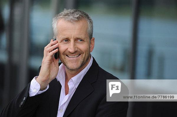 Reifer Mann mit Handy und Lächeln