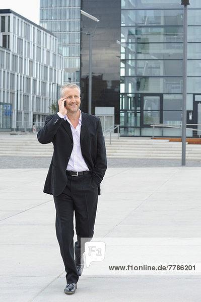 Reifer Mann  der im Finanzviertel spazieren geht und das Handy benutzt.