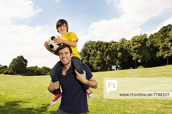 Vater trägt Sohn auf Schultern mit Fußball