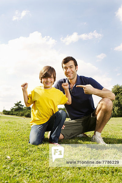 Vater zeigt auf den Sohn  der die Muskeln beugt.