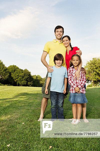 Porträt einer Familie mit zwei Kindern auf Rasen stehend