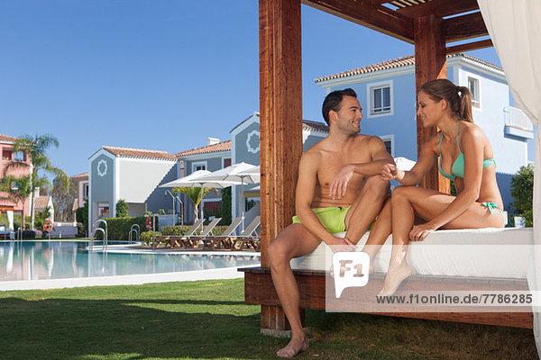 Junges Paar entspannt auf der Sonnenliege im Urlaubsort