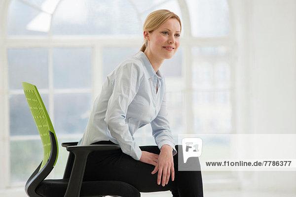 Geschäftsfrau auf Bürostuhl sitzend