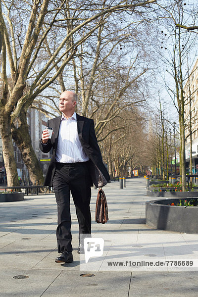 Erwachsener Geschäftsmann  der auf dem Bürgersteig mit Kaffee läuft