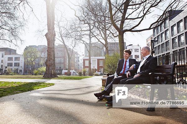 Zwei Geschäftsleute sitzen auf einer Parkbank.
