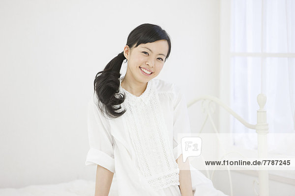 Young woman sitting on a bed