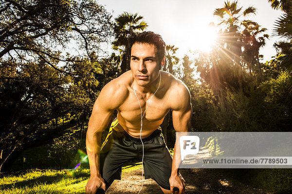 Young man exercising in forest resting