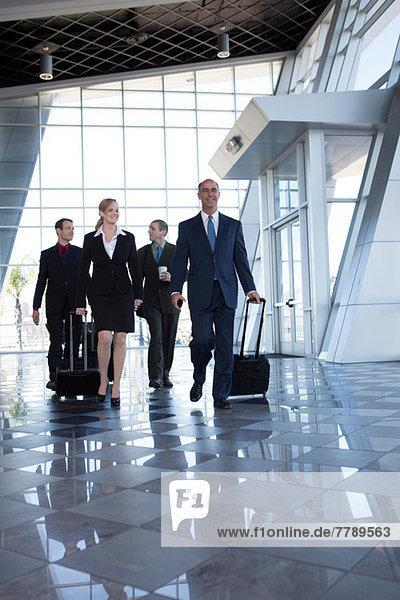 Geschäftsleute  die mit Koffern durch den Flughafen laufen