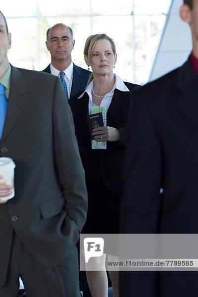 Geschäftsfrau in der Warteschlange mit Reisepass