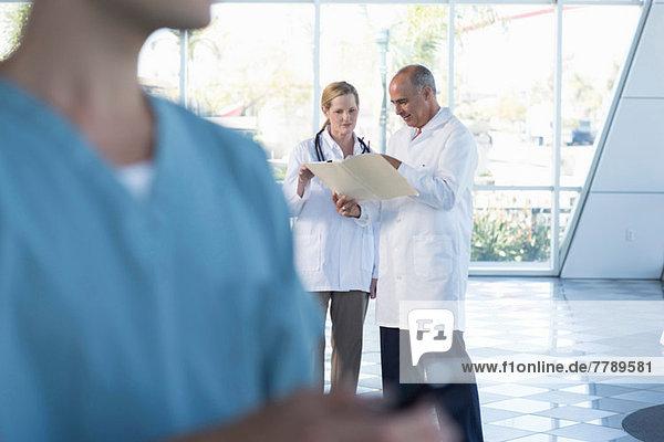 Zwei Ärzte diskutieren über Krankenakten