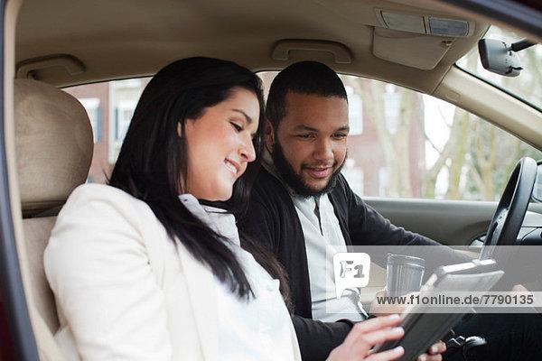 Junges Paar im Auto mit digitalem Tablett